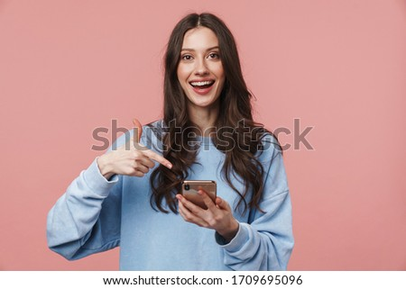 Image of delighted nice woman using cellphone and pointing finger aside Stock photo © deandrobot