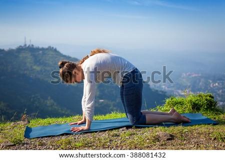 Sporty fit woman practices yoga asana Marjariasana outdoors Stock photo © dmitry_rukhlenko