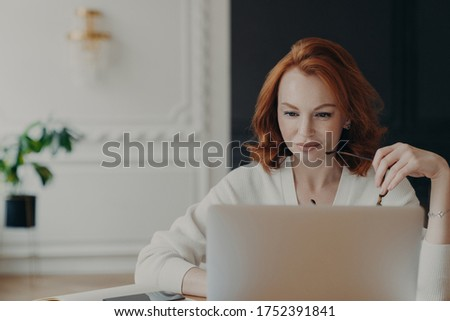 Photo of serious redhead woman journalist concentrated at laptop computer, searches information for  Stock photo © vkstudio