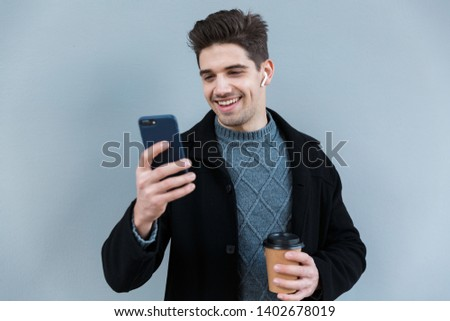 Image of young man wearing earpods holding smartphone over white Stock photo © deandrobot