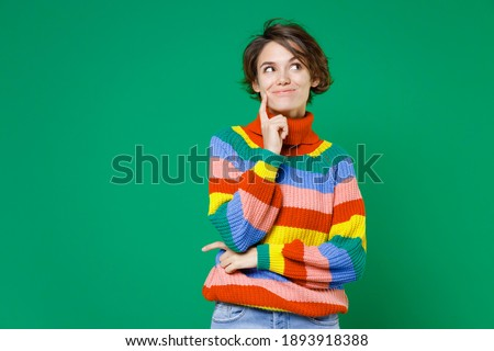 Thoughtful pretty casual brunette standing with hand on chin  Stock photo © wavebreak_media