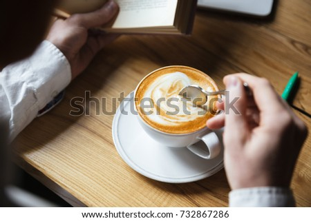Cropped photo of man in white shirt stirring coffee while readin Stock photo © deandrobot