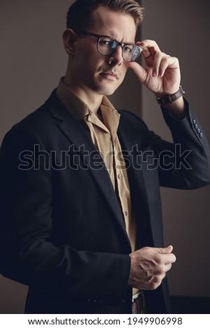 Portrait of confident handsome happy elegant responsible businessman with open hands on black backgr Stock photo © Traimak