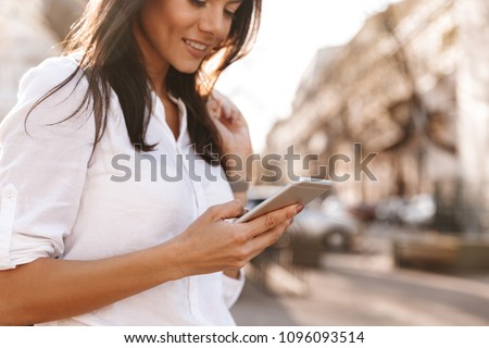 cropped imagge of pleased brunette woman in shirt using smartphone stock photo © deandrobot