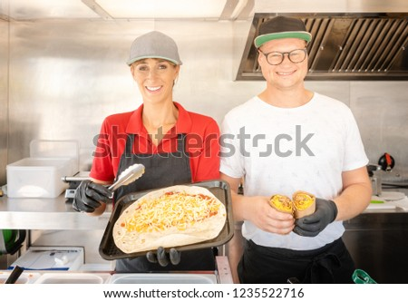 Woman and man chefs showing a meal they prepared in a food truck Stock photo © Kzenon