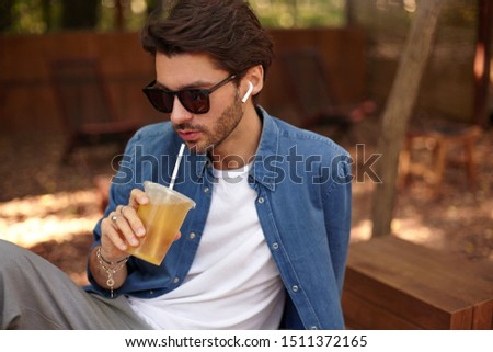 Stock photo: Photo of handsome man 30s wearing sunglasses, drinking takeaway