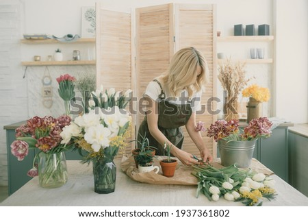 Smilling girl florist with creative bouquet from fresh flowers roses in a paper on a light backgroun Stock photo © artjazz