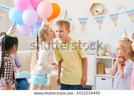 cute little girl in casualwear whispering something to boy while playing game stock photo © pressmaster