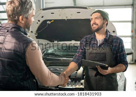 Mature professional repairman of car maintenance service standing by workbench Stock photo © pressmaster