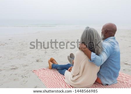 Casal de idosos sessão cobertor praia luz do sol Foto stock © wavebreak_media