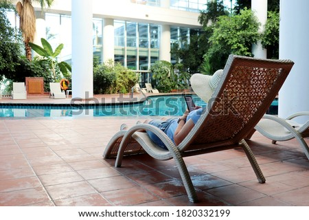 Woman with phone lounging near blue swimming pool on hotel terrace Stock photo © dash