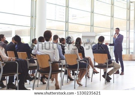 front view of handsome mixed race businessman speaking at business seminar with diverse business peo stock photo © wavebreak_media
