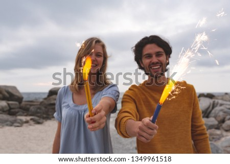 Portrait of young Caucasian couple playing with fire cracker while standing at beach. They are smili Stock photo © wavebreak_media