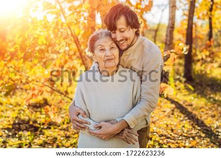 Grandmother and adult grandson hugging in autumn park Stock photo © galitskaya