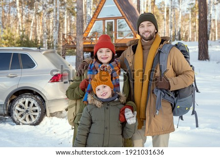 Two happy girls in winterwear standing by young man with black retriever Stock photo © pressmaster