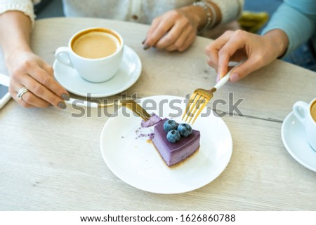 Hands of young friendly women with forks taking piece of tasty blueberry cake Stock photo © pressmaster