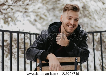 Outdoor shot of happy smiling bearded male in warm jacket and ha Stock photo © vkstudio
