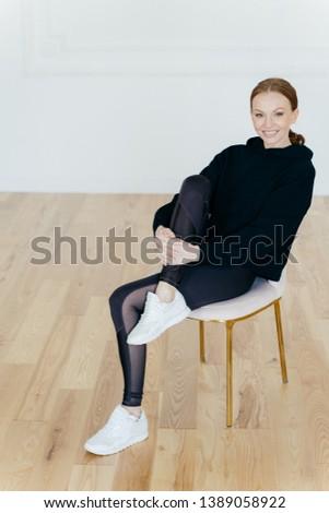 Young satisfied red haired woman raises leg, wears black hoody and leggings, white sneakers, has mak Stock photo © vkstudio