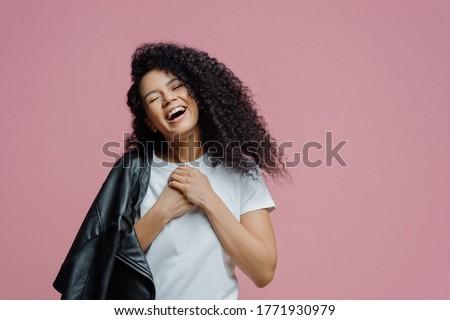 Carefree cheerful Afro American woman wears white jacket, keeps arm folded, looks aside, has charmin Stock photo © vkstudio