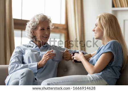 Smiling woman with tender smile, holds cup of tea or coffee, enjoys good rest, poses in cozy cafe or Stock photo © vkstudio