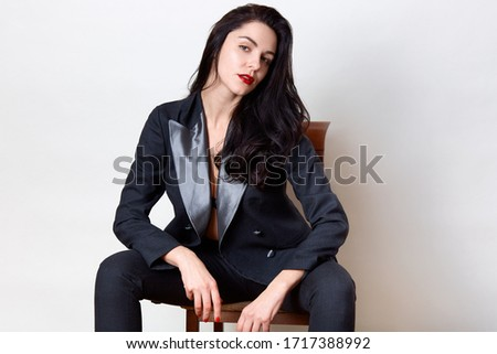 Horizontal shot of attractive dark haired female with red painted lips, dressed in black leather jac Stock photo © vkstudio