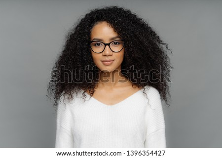 Beautiful dark skinned female model with crisp hair, looks down, dressed in casual white t shirt, bl Stock photo © vkstudio