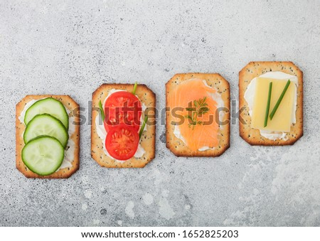 Various healthy crackers with salmon and cheese, tomato and cucumber on marble board on light kitche Stock photo © DenisMArt