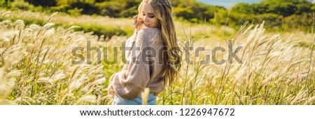Young beautiful woman in autumn landscape with dry flowers, wheat spikes. Fashion autumn, winter. Su Stock photo © galitskaya
