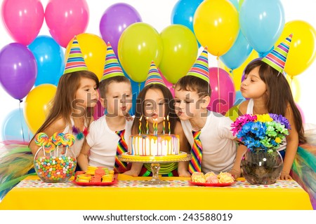 Small kids celebrate birthday party, blow candles on cake, gather at festive table, have good mood,  Stock photo © vkstudio