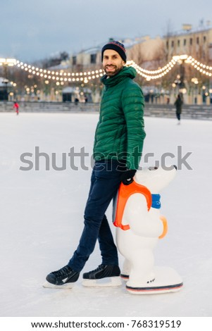 Portrait of cheerful bearded male stands near skate aid, going t Stock photo © vkstudio