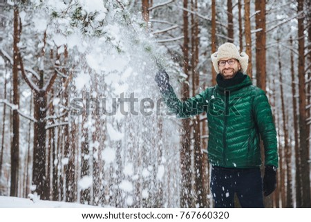 Portrait of cheerful handsome male wears fur cap with ear flap and yellow and green jacket, throws s Stock photo © vkstudio