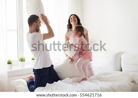 People, family and bedding concept. Cheerful young smiling mother and her daughter embrace each othe Stock photo © vkstudio