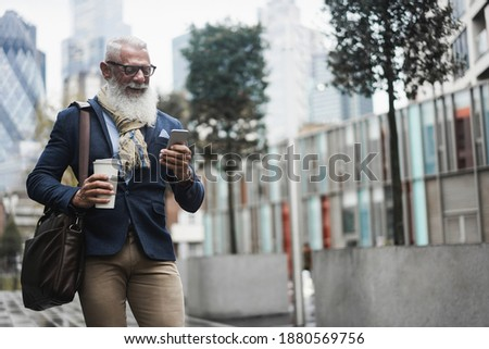 Image of mature focused businessman using cellphone while standing Stock photo © deandrobot
