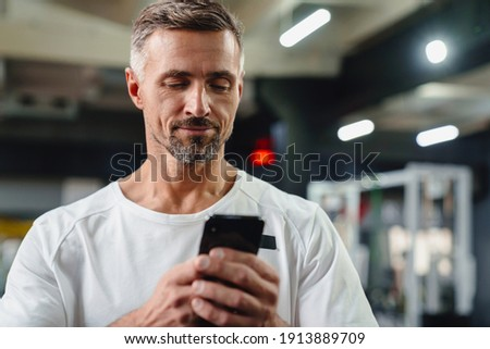 Image of pleased unshaven sportsman using cellphone and smiling Stock photo © deandrobot