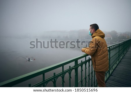 Pensive man wears protective mask against new coronavirus from China, wrapped scarf around neck, loo Stock photo © vkstudio
