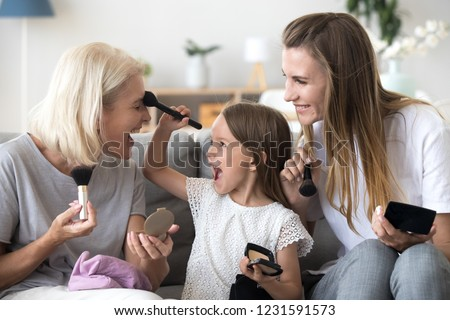 Positive young woman apply blush with brush holding mirror. Stock photo © deandrobot