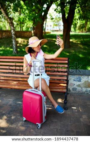Blogger woman in straw hat and removed mask holds on her head, in the park Stock photo © Illia