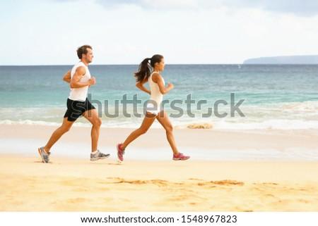 Couple runners running on beach. Interracial young adults asian woman, caucasian man, training cardi Stock photo © Maridav