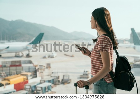 Airport girl passenger on mobile phone waiting for delayed flight sitting at terminal gate with lugg Stock photo © Maridav