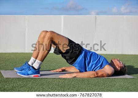 Fitness man doing bodyweight glute floor bridge pose yoga exercise. Fit athlete exercising glutes mu Stock photo © Maridav