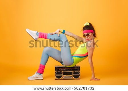 Playful young woman athlete sitting on retro boombox and posing Stock photo © deandrobot