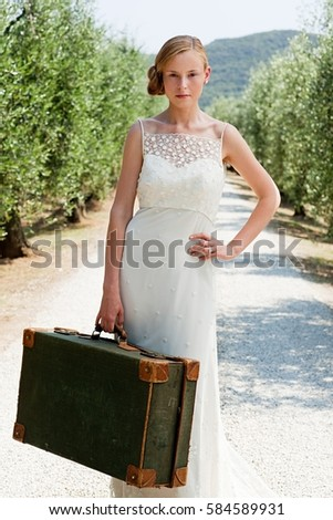 Bride with suitcase on country road, hand on hip Stock photo © IS2