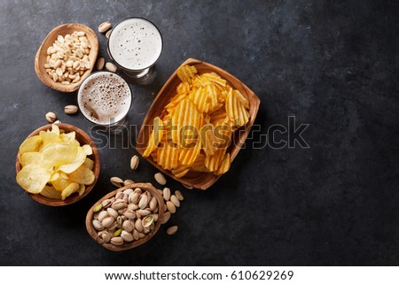 Glass of lager beer with pistachios nuts on stone board on black background. Beer and snack. Space f Stock photo © DenisMArt