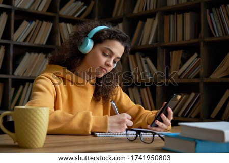 A young girl in headphones sits at a table in the office, holds a pencil in her hand and works with  Stock photo © Traimak