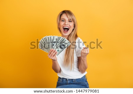 Woman posing isolated over yellow background holding money covering face. stock photo © deandrobot