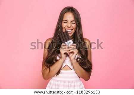 Photo of joyous woman 20s wearing dress smiling and eating choco Stock photo © deandrobot