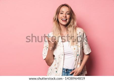 Cute młodych pani stwarzające odizolowany różowy Zdjęcia stock © deandrobot