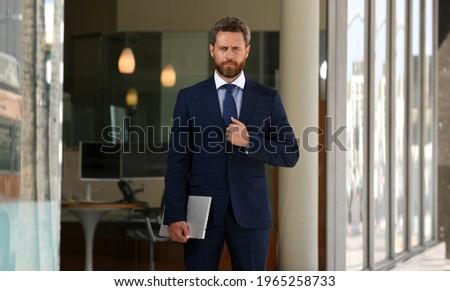 zakenman · met · behulp · van · laptop · mobieltje · kantoor · geconcentreerde · jonge - stockfoto © deandrobot