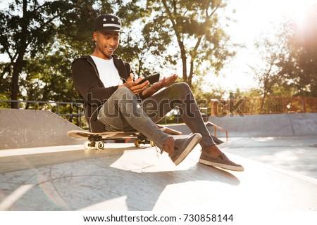 Derűs fiatal görkorcsolyázó fickó ül park Stock fotó © deandrobot