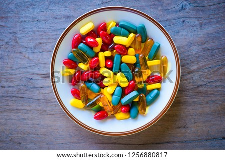 fish from colorful pills and tablets on a white plate and womans hand with chopsticks on a blue bac stock photo © artjazz